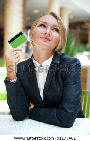 Closeup portrait of cute young business woman smiling while holding credit card and daydreaming - stock photo