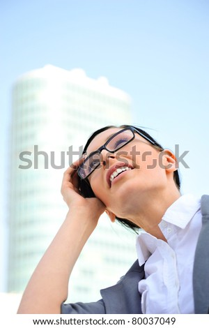 Closeup portrait of cute young business woman wearing glasses smiling. Outdoor against office building and beautiful view - stock photo
