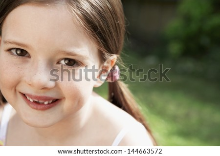 Closeup portrait of cute young girl smiling in park - stock photo