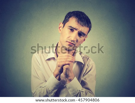 Closeup portrait of desperate young man showing clasped hands, please forgive me isolated on gray wall background. Human emotion facial expression feelings, body language - stock photo