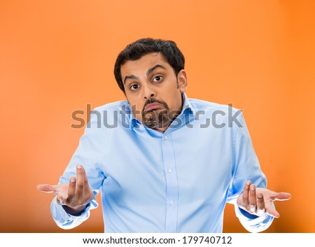 Closeup portrait of dumb, clueless young man, student, worker arms out asking what's the problem who cares so what, I dont know, isolated on yellow background. Negative human emotion facial expression