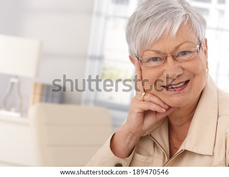 Closeup portrait of elderly woman looking at camera, smiling. - stock photo