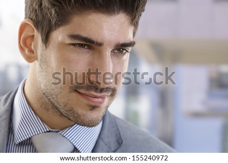 Closeup portrait of elegant handsome businessman looking away.