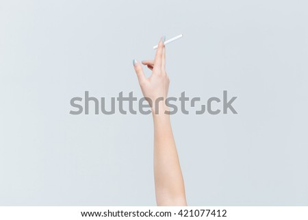 Closeup portrait of female hand holding cigarette isolated on a white background