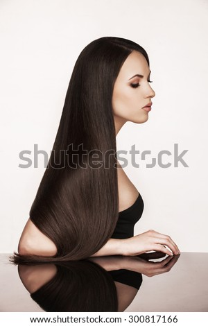 Closeup portrait of female posing in studio. Beautiful Woman with Long Healthy and Shiny Smooth Brown Hair. Hairstyle, haircare concept. - stock photo