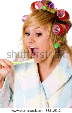 closeup portrait of funny housewife with curlers and toothbrush on white background - stock photo