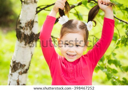 Closeup portrait of funny little toddler girl. Laughing child playing with her hair. Carefree cheerful baby. Beautiful girls face happily smiling. - stock photo