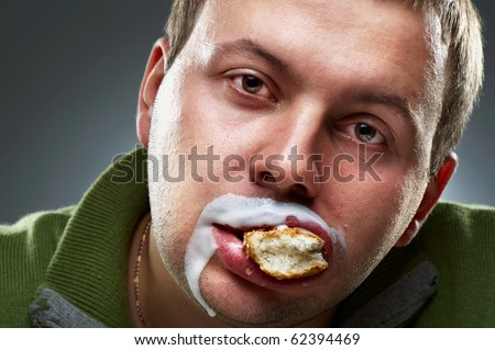 Closeup portrait of funny man. Yogurt traces on his lips, mouth full of bread - stock photo
