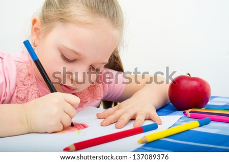 Closeup portrait of girl drawing with colorful pencils - stock photo