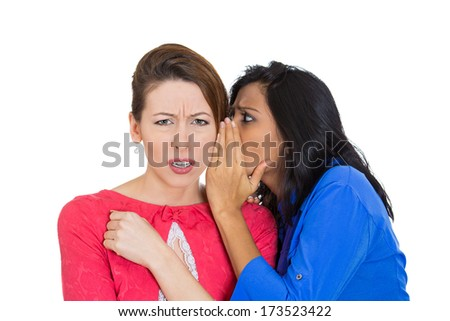 Closeup portrait of girl whispering into woman ear telling her something secret and disturbing. Shocked surprised disgusted annoyed mad response. Negative human emotions facial expression feelings - stock photo