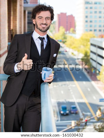 Closeup portrait of good looking smiling, happy businessman giving you a thumbs up, enjoying a drink, standing on his balcony, isolated on a city background. Urban life style, living of an executive - stock photo