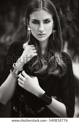Closeup portrait of gorgeous young woman with unusual earrings. black and white
