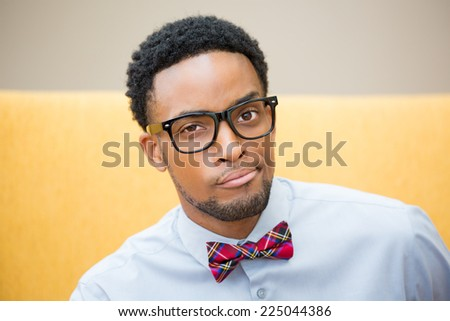Closeup portrait of handsome cocky guy with big black glasses and blue shirt looking at you camera gesture skeptically. Negative human emotion facial expression feeling - stock photo