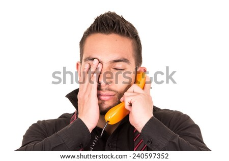 closeup portrait of handsome hispanic man talking on corded retro phone gesturing disappointment isolated on white - stock photo