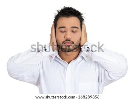 Closeup portrait of handsome young man covering his ears with hands eyes and mouth closed, isolated on white background.  Hear no evil concept. Human emotions facial expressions, - stock photo