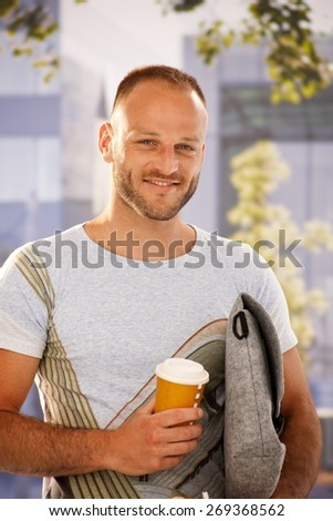 Closeup portrait of handsome young man holding bag and coffee in hands outdoors, smiling happy, looking at camera. - stock photo