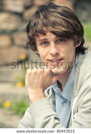 Closeup portrait of handsome young man outdoors - stock photo