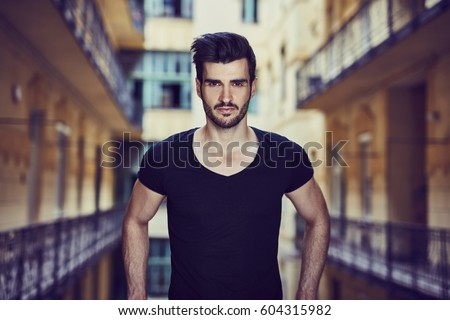 Closeup portrait of handsome young man standing in old house.