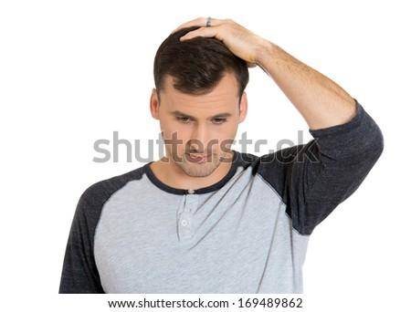 Closeup portrait of handsome young man thinking daydreaming deeply about something hand on head looking downwards, isolated on white background. Negative emotion facial expression feeling