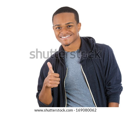 Closeup portrait of handsome young smiling man in black hoodie giving one thumbs up at camera sign isolated on white background. Positive human emotions facial expression feelings. Symbols - stock photo
