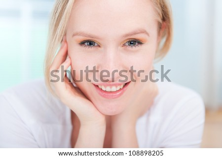 Closeup portrait of happy attractive young woman resting her head on her hand