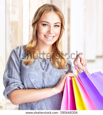 Closeup portrait of happy customer with colorful paper bag in great mall, attractive girl enjoying shopping, buying gifts, spending money concept - stock photo