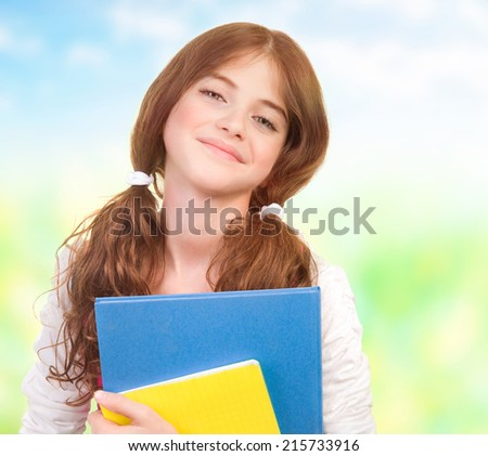 Closeup portrait of happy cute teen girl with textbooks having fun outdoors, back to school, education concept - stock photo