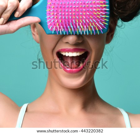 Closeup portrait of happy fashion brunette woman close eyes with colorful pink blue big hair brush on modern mint background - stock photo