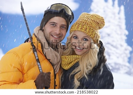 Closeup portrait of happy loving couple standing in snowfall, skiing. - stock photo