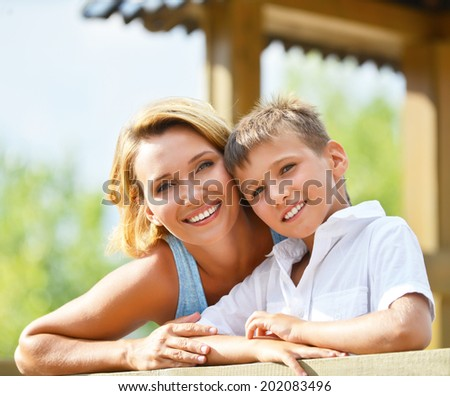 Closeup portrait of happy mother and son looking at camera at the park. - stock photo