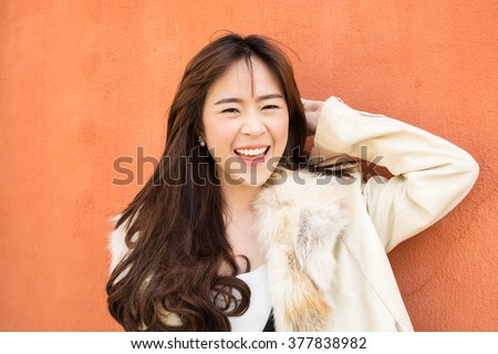 Closeup portrait of happy pretty young woman in fur pink dress orange background.  Positive human emotion facial expression feelings, attitude, perception - stock photo