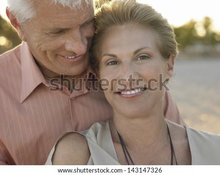 Closeup portrait of happy senior couple spending romantic time on beach - stock photo