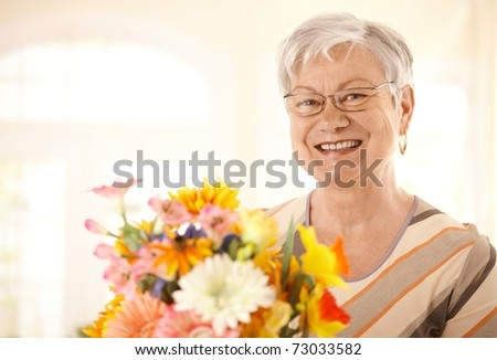 Closeup portrait of happy senior woman holding flowers looking at camera, smiling.? - stock photo