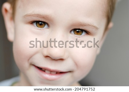 Closeup portrait of happy smiling little cute boy looking to camera on light background - stock photo