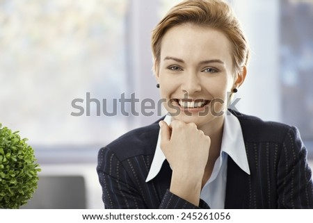 Closeup portrait of happy smiling young businesswoman in office. - stock photo