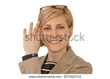 Closeup portrait of happy young blonde woman smiling, looking at camera sweeping aside hair from face. - stock photo