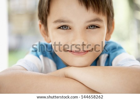 Closeup portrait of happy young boy outdoors - stock photo