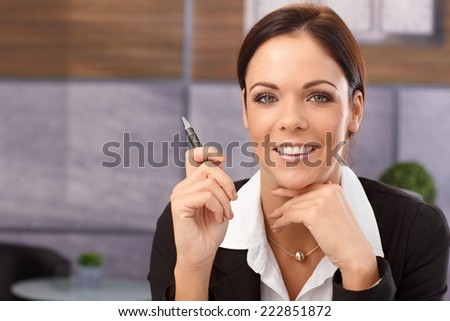Closeup portrait of happy young businesswoman smiling in office, holding pen. - stock photo