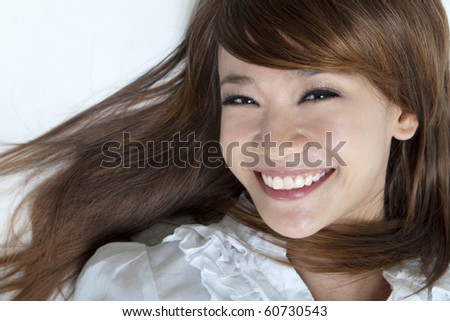 Closeup portrait of happy young girls lying on ground - stock photo
