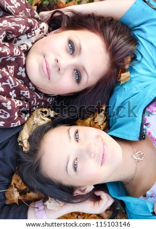 Closeup portrait of happy young girls lying on ground with their heads together - stock photo