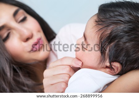 Closeup portrait of happy young mother touching face of her adorable little child, enjoying motherhood, family love concept - stock photo