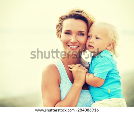 Closeup portrait of happy young mother with little son standing on the beach. - stock photo