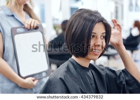 Closeup portrait of hispanic latin girl woman sitting in chair in hair salon looking in mirror at her new haircut, short bob pixie, happy joy emotion - stock photo
