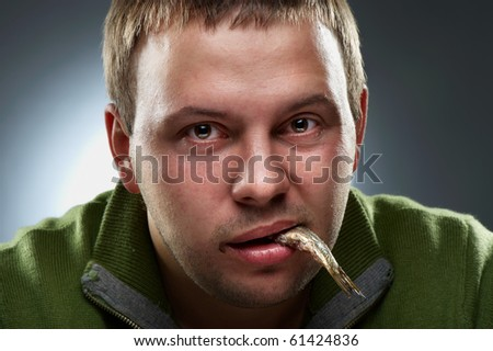 Closeup portrait of hungry man with fish in mouth - stock photo