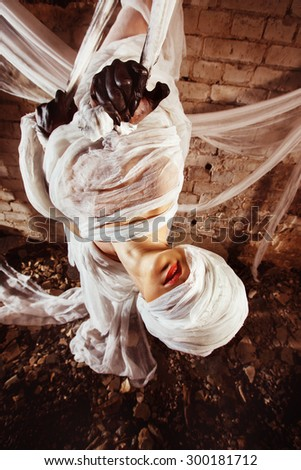 Closeup portrait of insane creature in cocoon hanging from a ceiling at bricks wall background. - stock photo
