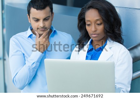 Closeup portrait of intellectual healthcare professional with white labcoat, looking at record, discussing findings with young patient, using digital technology, isolated hospital clinic background - stock photo