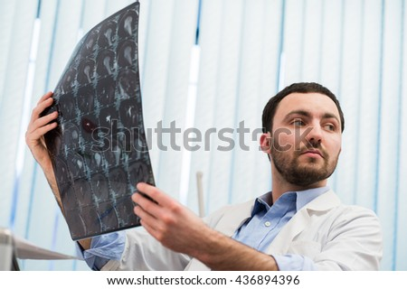 Closeup portrait of intellectual man healthcare personnel with white labcoat, looking at brain x-ray radiographic image, ct scan, mri, clinic office background. Radiology department - stock photo