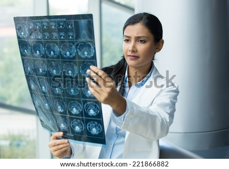 Closeup portrait of intellectual woman healthcare personnel with white labcoat, looking at full body x-ray radiographic image, ct scan, mri, isolated hospital clinic background. Radiology department - stock photo