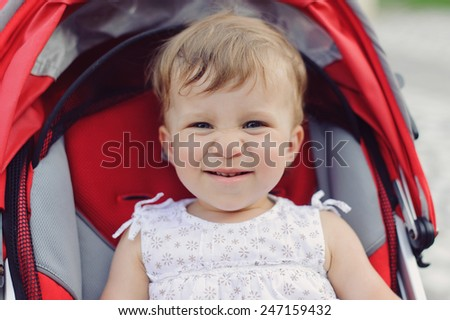 closeup portrait of laughing girl in stroller
