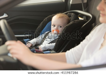 Closeup portrait of little baby boy sitting in car at safety seat - stock photo